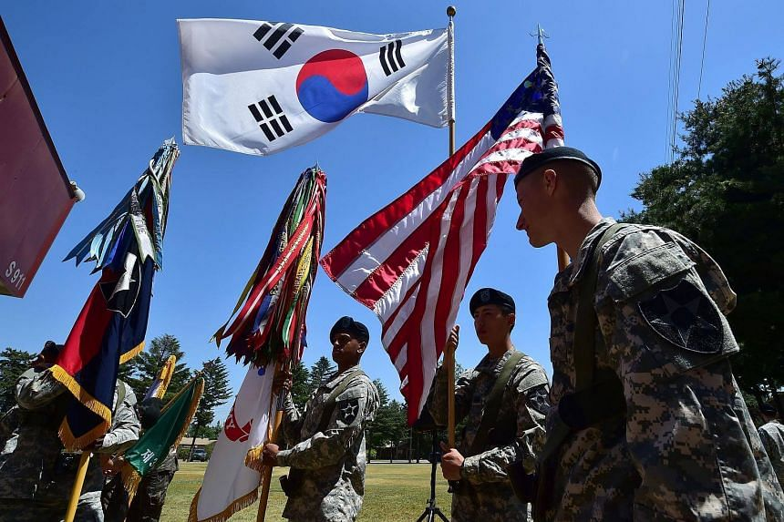 US soldiers holding the flags of South Korea and the US before a South Korea-US Combined Division activation ceremony at an US Army base.
