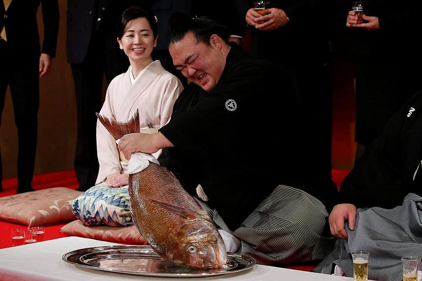 Japanese sumo wrestler Kisenosato holds a red sea bream as he sits beside the wife of his stablemaster at a ceremony yesterday after being promoted to the topmost rank of yokozuna. He is the first Japanese-born wrestler to earn the distinction since