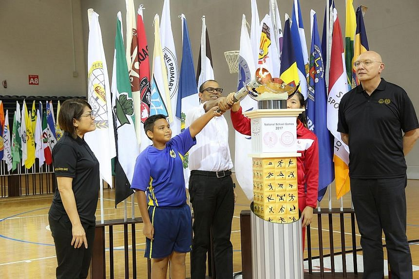 Minister of State for Education Dr Janil Puthucheary, with the help of Sembawang Primary School's Ricqiey Dannyall and Singapore Sports School's Crystal Wong (in red) lighting the NSG cauldron to mark the Games' opening.