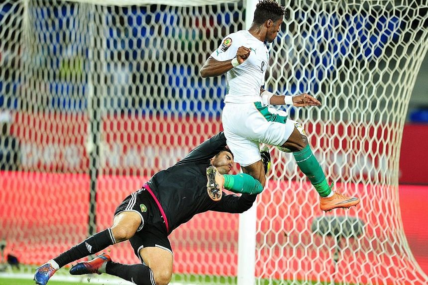 Ivory Coast forward Wilfried Zaha (No. 9) having his shot saved by Morocco goalkeeper Monir El Kajoui. Zaha could not breach the opposition backline as defending champions Ivory Coast were dumped out of the Africa Nations Cup, following a 1-0 loss to