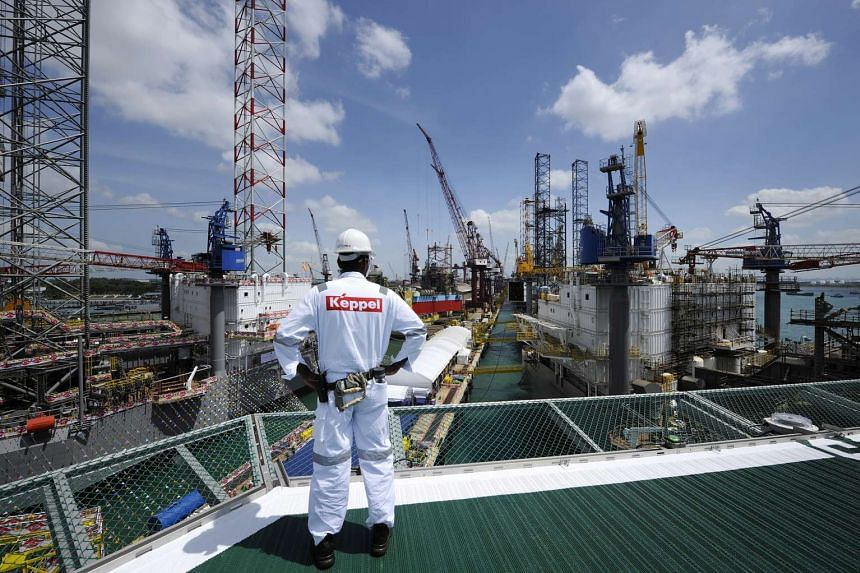A Keppel Corp. employee looks out towards jack up rigs under construction at the Keppel FELS shipyard in Singapore.