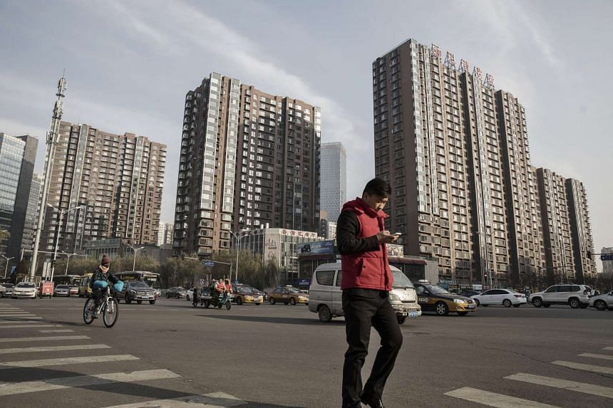 A pedestrian uses a smartphone as he crosses a road in front of residential buildings in Beijing, China.