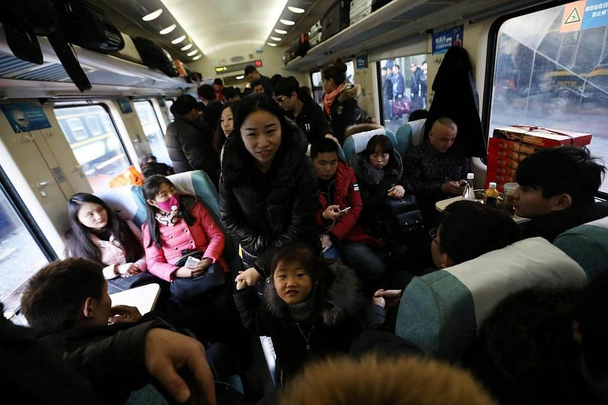 Chinese travelers getting into a crowded train at the Beijing Railway Station in Beijing, China on Jan 22, 2017.