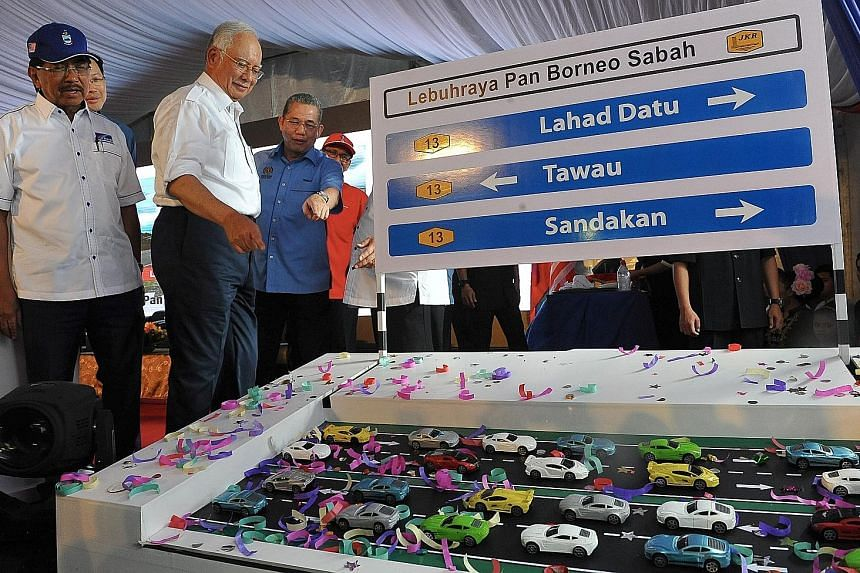 Prime Minister Najib Razak (second from far left) with Sabah Chief Minister Musa Aman (in blue cap) at an event in Sabah last December. Mr Najib has reportedly agreed for an early election to be called in the state. Analysts expect this to pave the w