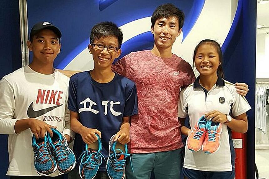 National marathoner Soh Rui Yong (second from right) with local student-athletes (from left) Muzhaffar Shah of Republic Polytechnic, Lin Jing Chao of River Valley High School and Dora Shoo of Bendemeer Secondary at the Asics store at Suntec City yest