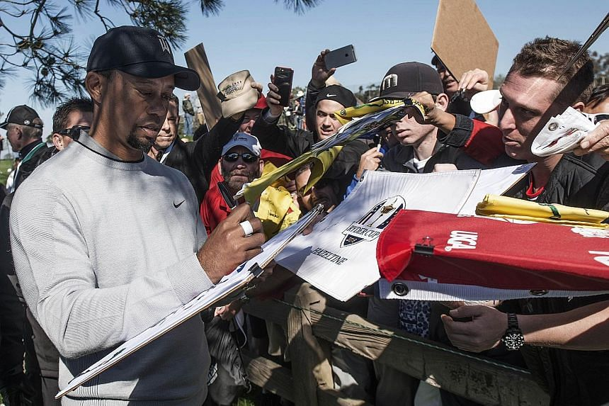 """Tiger Woods signing autographs for fans following Wednesday's pro-am round before the Farmers Insurance Open at Torrey Pines, California. The US golfer says he is ready to """"win tournaments"""" once again."""