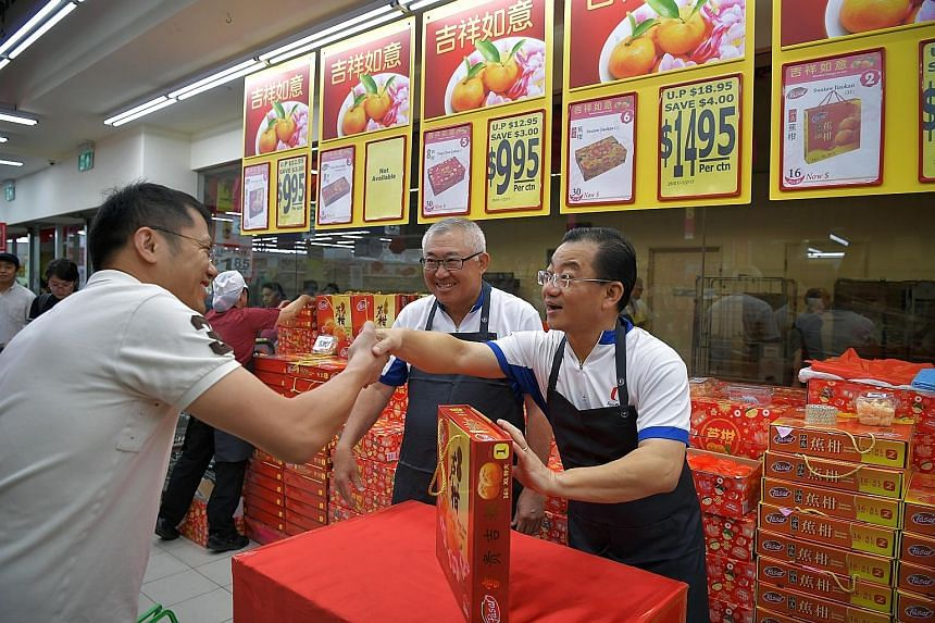 FairPrice chairman Mr Chin (centre) and chief executive Mr Seah (right) manning the mandarin orange booth at a Toa Payoh outlet yesterday. Mr Seah said that attachments at the stores help office staff to understand the challenges faced by front-line