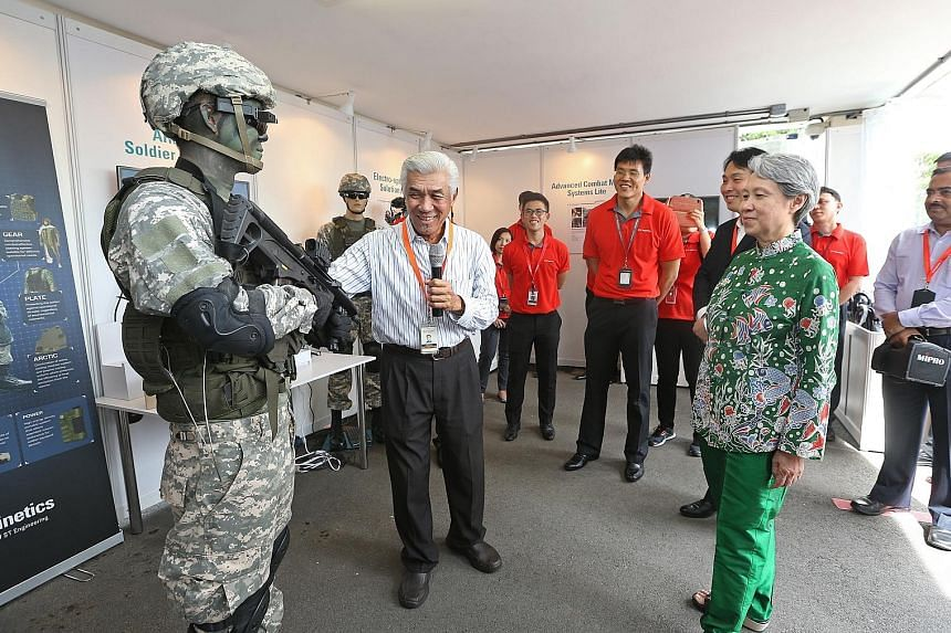 Founding chairman of ST Engineering Ho Ching being introduced to the Ariele Soldier System by Mr Patrick Choy, the firm's executive vice-president, strategic projects, at its anniversary event yesterday.