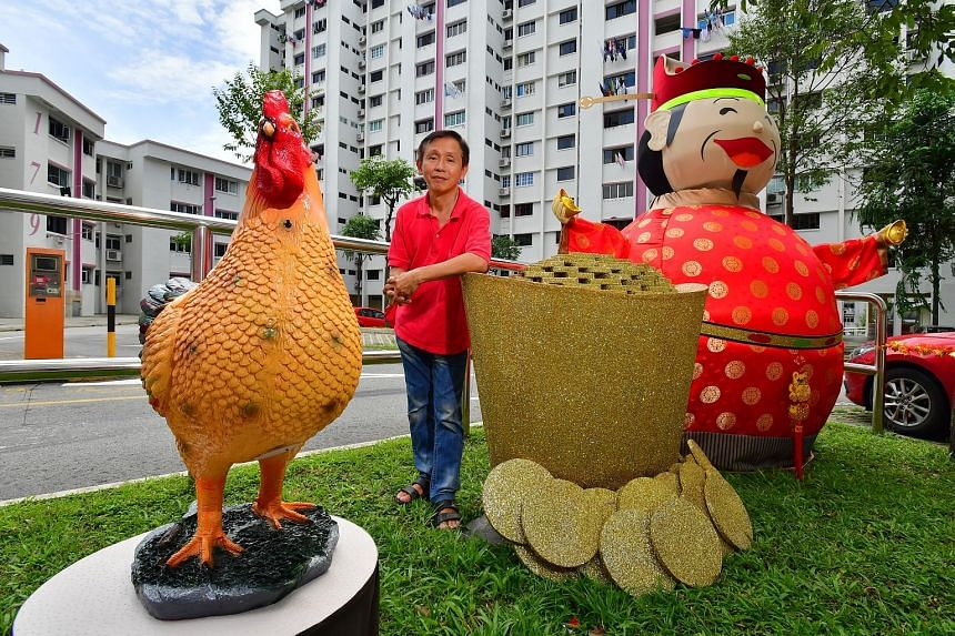 The festive decor at Block 179 prompts Mr Alan Tan (far right) to have a photo taken with his friend, Mr Yeow Thiam Teck, and the rooster statue. Mr Tan with his handiwork near Block 179, Woodlands Street 13. The carpenter has lived in the estate for