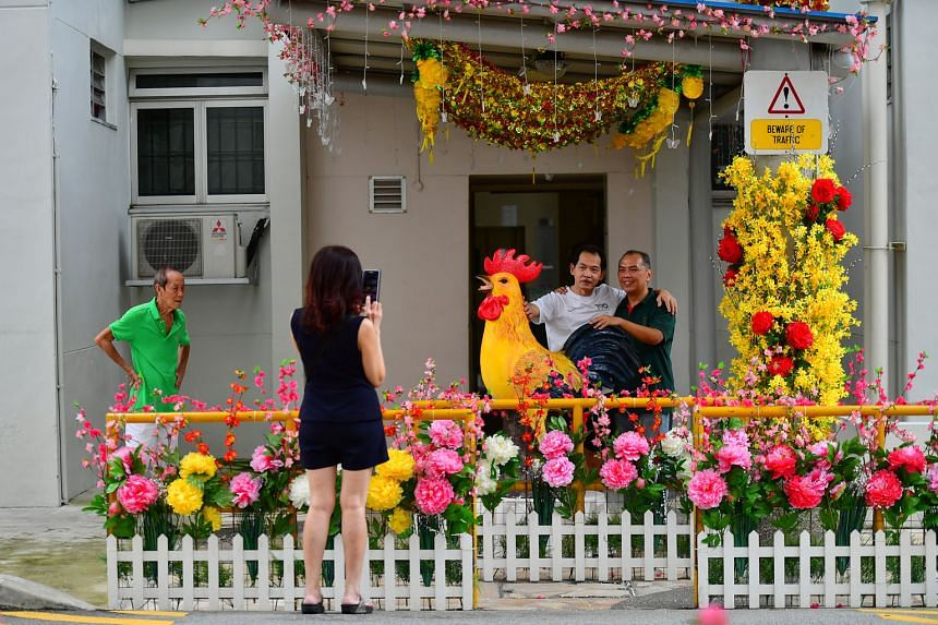 The festive decor at Block 179 prompts Mr Alan Tan (far right) to have a photo taken with his friend, Mr Yeow Thiam Teck, and the rooster statue.