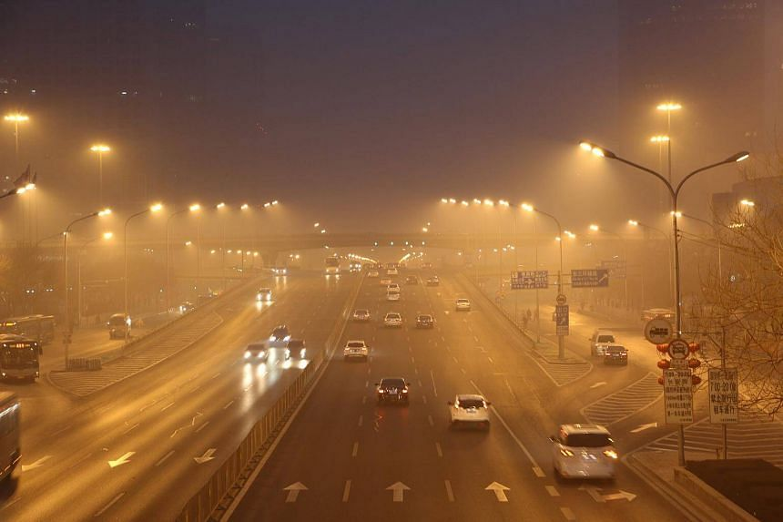 Cars drive along a street in smog during a polluted day in Beijing, China, on Jan 26, 2017.