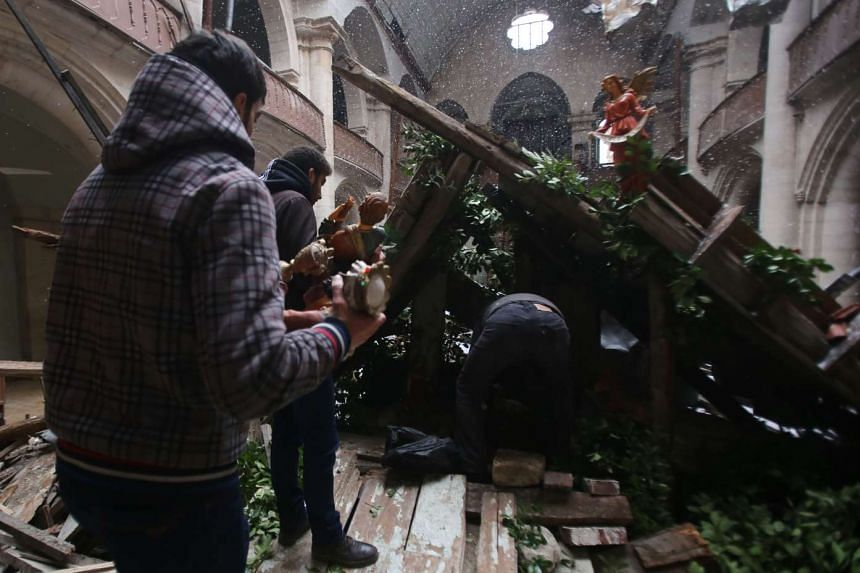 Cathedral committee members inspect the war damage to the Saint Elias Cathedral in eastern Aleppo, Syria, on Dec 21, 2016.