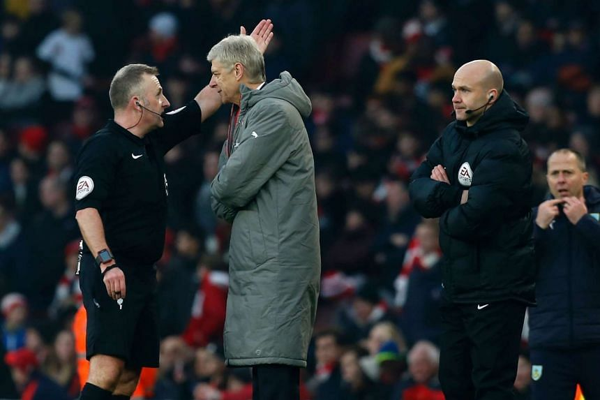 Arsenal's French manager Arsene Wenger (2nd left) is sent to the stands by English referee Jonathan Moss (left) as fourth official Anthony Taylor (right) looks on during the English Premier League football match between Arsenal and Burnley at the Emi