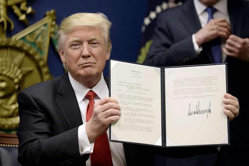 Trump holds up signed executive orders in Arlington, Virginia, on Jan 27, 2017.