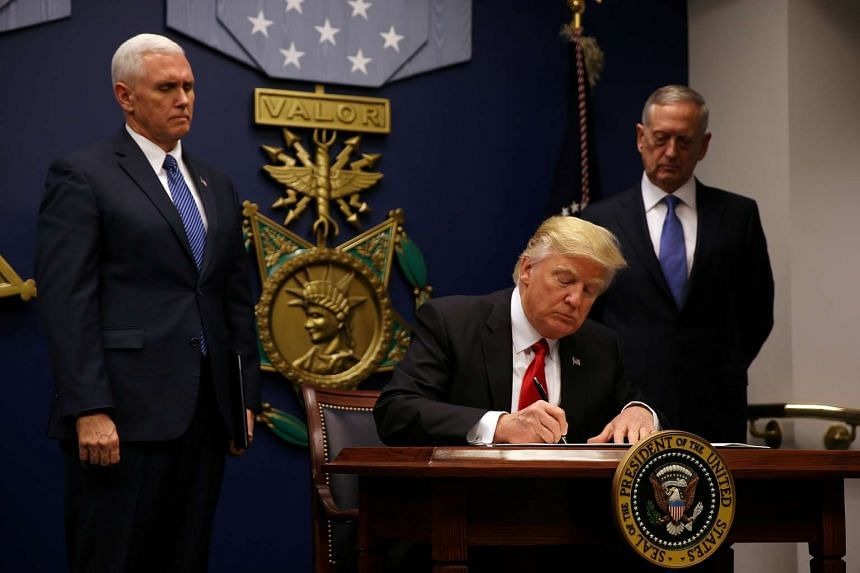 US President Donald Trump signing an executive order he said would impose tighter vetting to prevent foreign terrorists from entering the US.