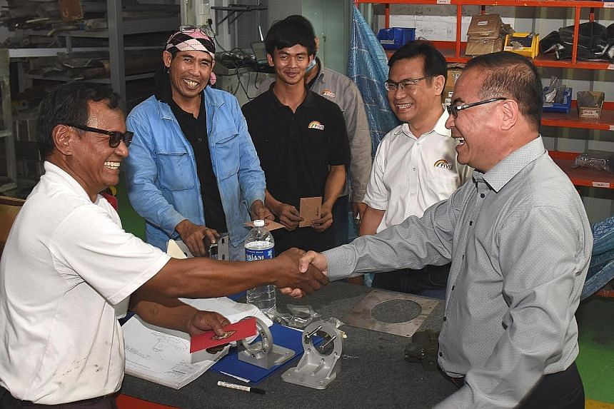 Five Aluminium Boat and Engineering managing director Edmund Long (at right) giving out red packets to his staff to thank them for their hard work and contributions in the past year.