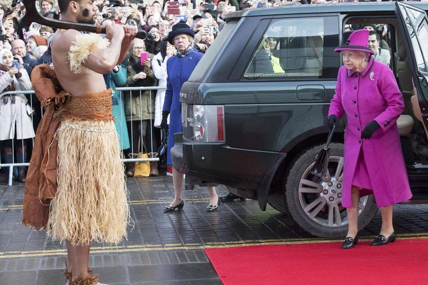 Queen Elizabeth is met by a man dressed in traditional costume as she arrives to view an exhibition on Fiji in Norwich, eastern England on Jan 27, 2017.