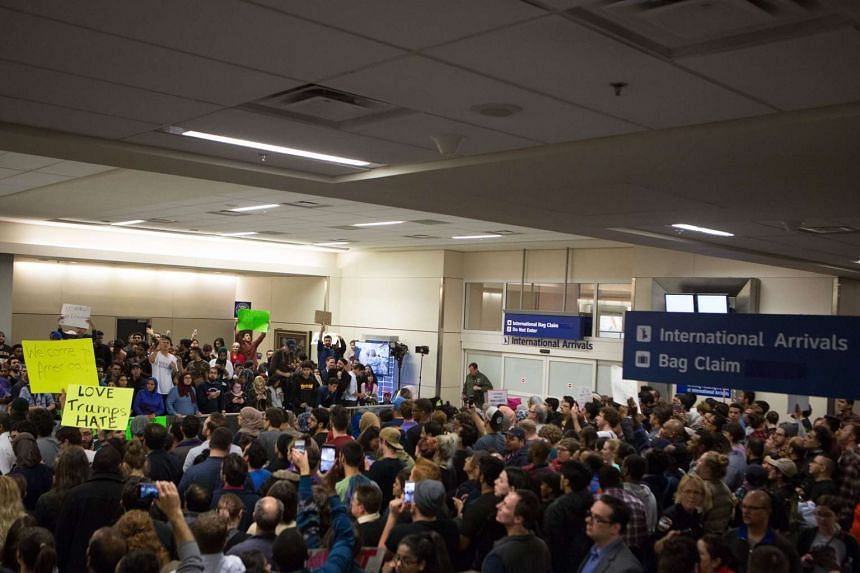Protesters gather to denounce President Donald Trump's executive order that bans certain immigration, at Dallas-Fort Worth International Airport on Jan 28, 2017 in Dallas, Texas.
