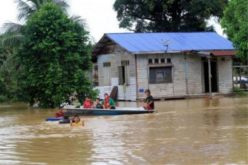 Residents in Kampong Sungai Ganchong, Pekan, wading through floodwaters with their boat on Sunday.