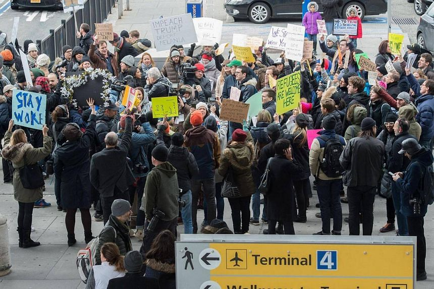 Protesters gathering at JFK International Airport's Terminal 4 to demonstrate against US President Donald Trump's executive order, on Jan 28, 2016, in New York.