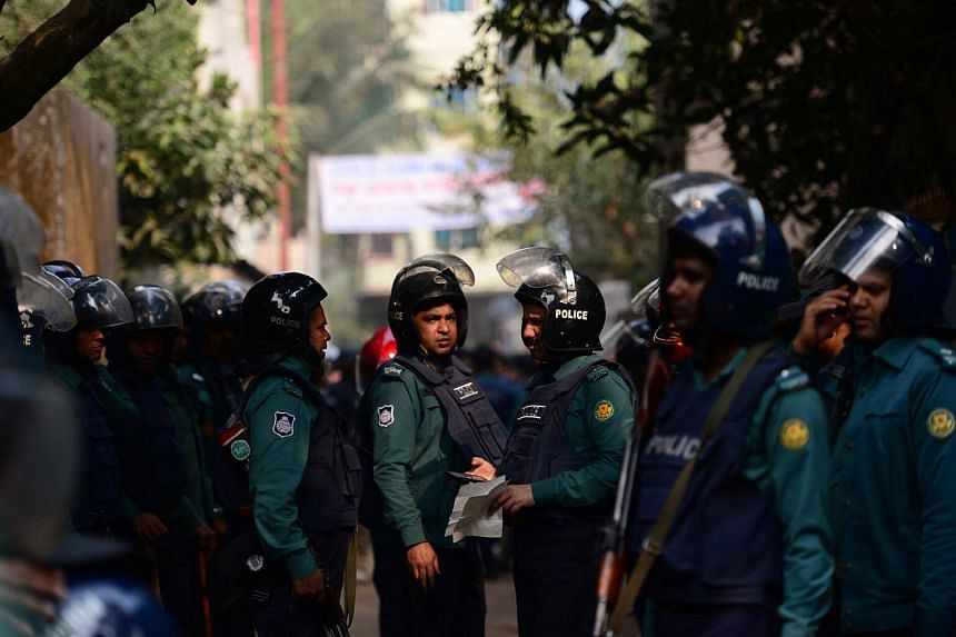 Bangladesh police officials stand alert at the scene of an operation to storm an alleged militant hideout in Dhaka, on Dec 24, 2016.