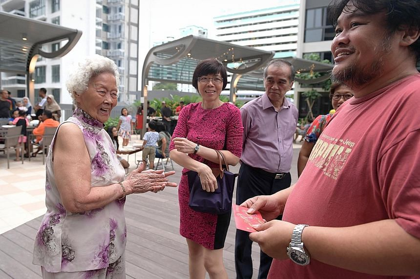 Mr Jaafar (at far right), 43, receiving a red packet from his aunt, Madam Teo Seat Lay (left), 85, yesterday. Mr Jaafar's mother, Madam Zawiah, who was adopted by a Malay family when she was an infant, sought to reconnect with her biological Chinese
