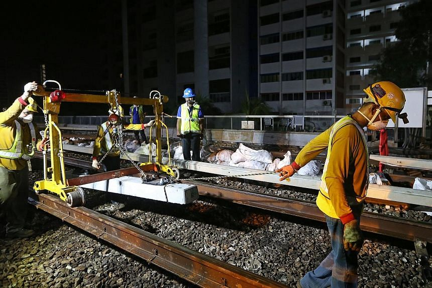 Workers replacing older timber sleepers with hardier concrete ones on the East-West Line last November. The four-year project to upgrade the sleepers on the North-South and East-West lines was completed last month.