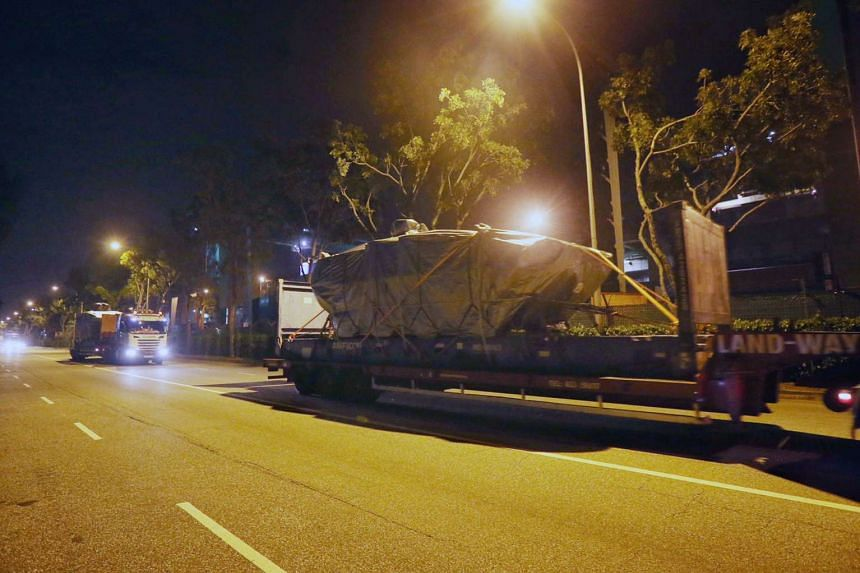 Two of the nine Terrex armoured vehicles, covered by tarpaulins, are seen along Harbour Drive on Monday (Jan 30) night, after they reached Singapore.
