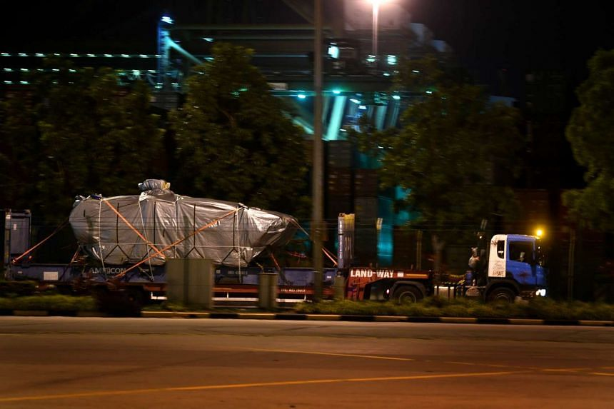 One of the nine Terrex armoured vehicles, covered by a tarpaulin, is seen being moved out at PSA Tanjong Pagar on Monday (Jan 30) night.