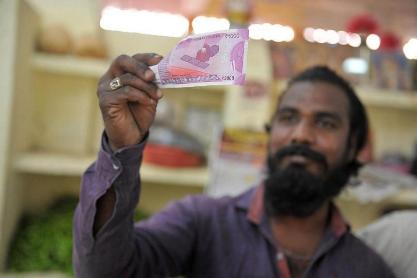 An Indian vendor holding up a 2000 rupee note at a vegetable market on the outskirts of Hyderabad, on Nov 21, 2016.