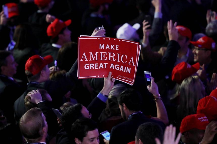 """An attendee holds up a sign in support of Donald Trump that reads """"Make America Great Again"""" during the election night event."""