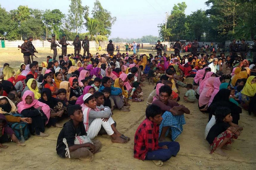 Rohingya Muslims from Myanmar, who tried to cross the Naf river into Bangladesh to escape sectarian violence, are kept under watch by Bangladeshi security officials in Teknaf.