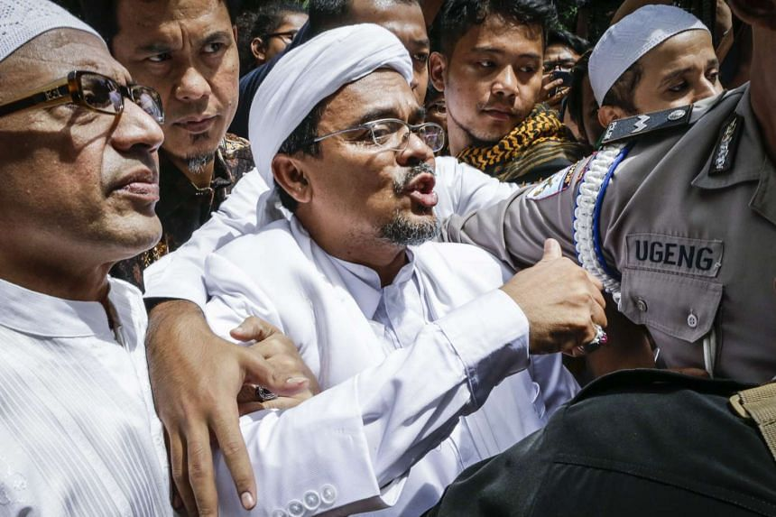 Indonesian cleric Habib Rizieq Shihab speaking while being escorted by police officers and supporters at the police headquarters in Jakarta on Jan 23, 2017.