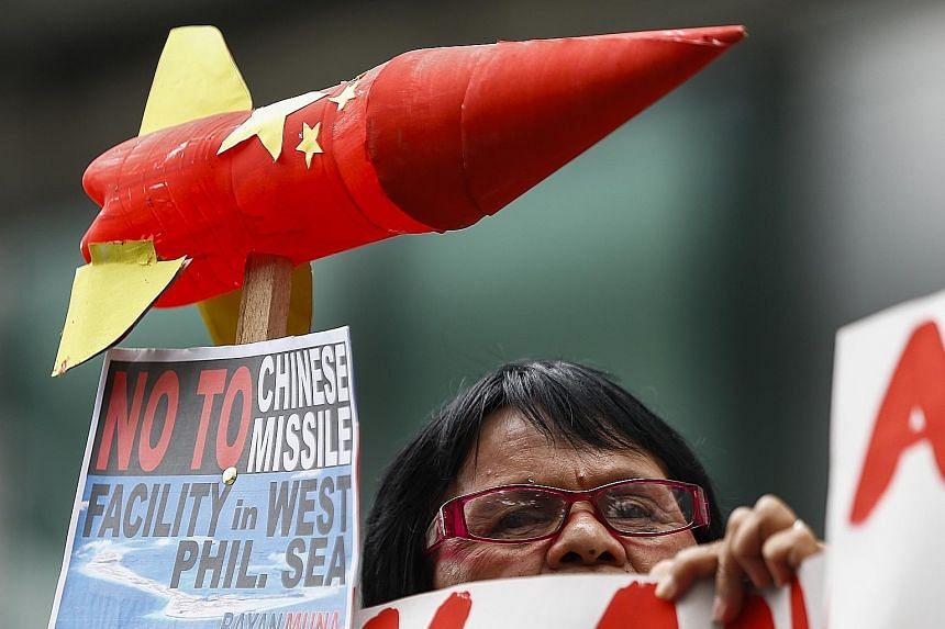 An activist protesting against Chinese military installations in the South China Sea, in Manila, last Tuesday. President Duterte said on Sunday that the US presence in his country is putting regional stability at risk and dragging the Philippines int