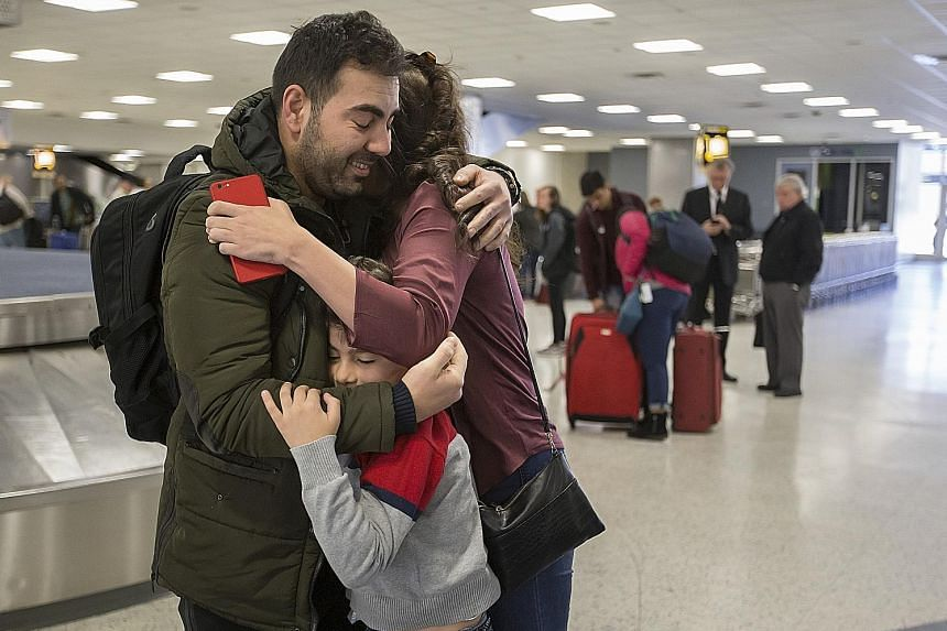 Baghdad-born accountant Haider Sameer Abdulkhaleq Alshawi back with his family at the airport in Houston on Sunday, after being detained in New York the previous day following Mr Trump's executive order on immigration.