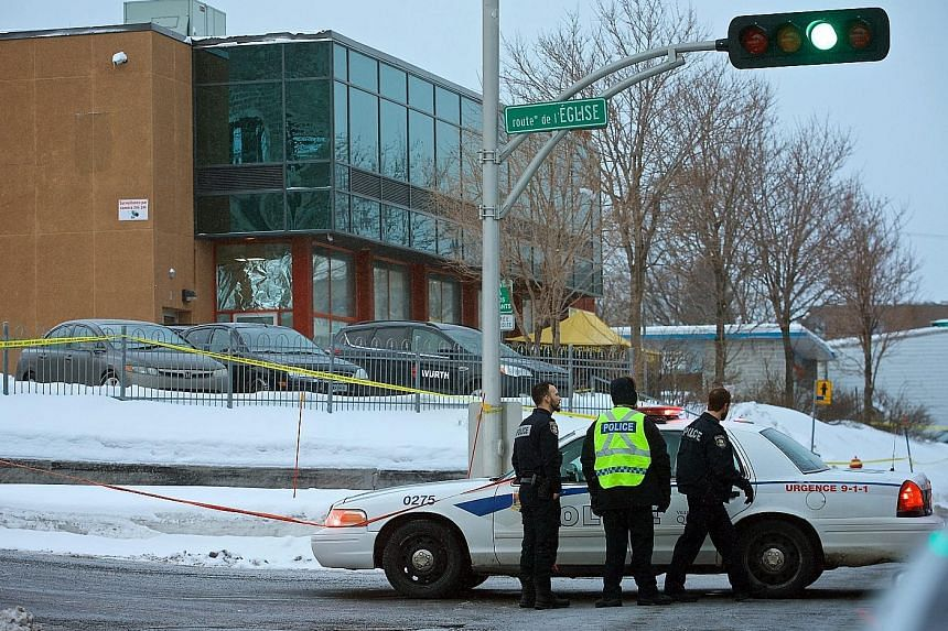 Police officers patrolling the area around the Islamic Cultural Centre in Quebec City yesterday, after Sunday's shooting during evening prayers. The attack came as Canada vowed to open its arms wide to Muslims and refugees after US President Donald T