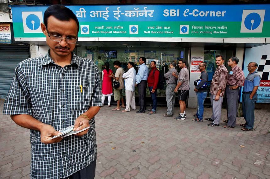 A man counts Indian rupee banknotes after withdrawing them from State Bank of India ATM in Kolkata, India on November 11.