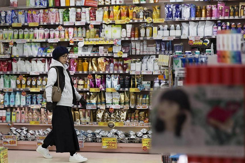 A shopper walks past personal care products displayed in a drug store in Kitakyushu, Japan.