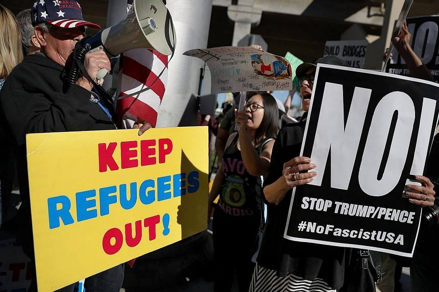 A protester faces off with a supporter of US President Donald Trump during a demonstration against the immigration ban that was imposed by President Trump at Los Angeles International Airport on Jan 29, 2017.