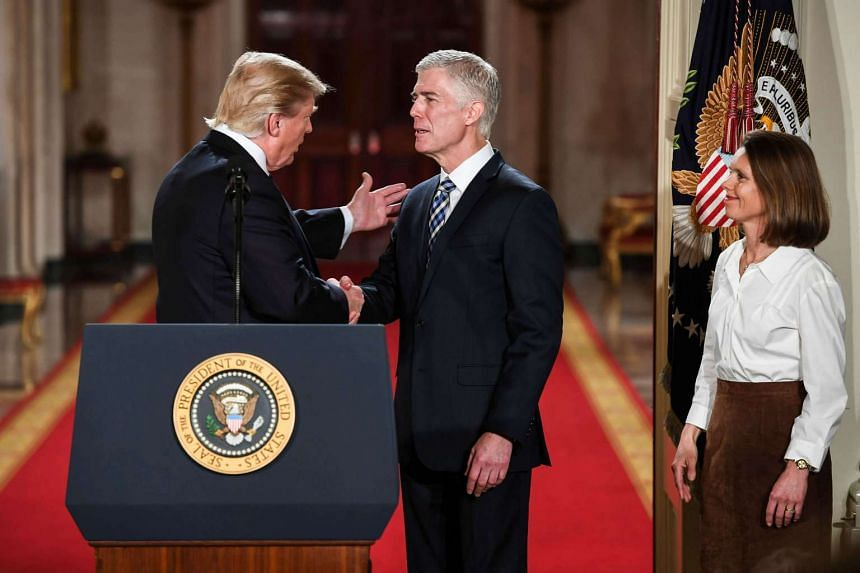 After announcing his Supreme Court nomination, US President Donald Trump shakes the hand of Judge Neil Gorsuch in the East Room at the White House.