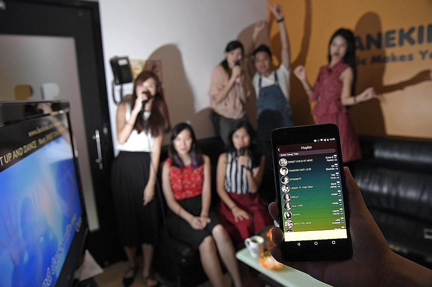 Customers having a karaoke session at Manekineko using the firm's MyKara app. The karaoke chain offers secured Wi-Fi for customers to surf the Internet and to control the song-selection system.