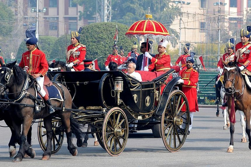 Indian President Pranab Mukherjee (in white) leaving Parliament on the opening day of the Budget session yesterday. Indian Finance Minister Arun Jaitley is expected to present the Budget today. In a survey published yesterday, the government lowered
