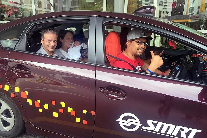 Mr Hamid, his wife del Rosario Ortiz and baby Kifah being given a free ride home in Mr Mohamad's SMRT cab yesterday, courtesy of the company. On Monday, she gave birth to Kifah in the same taxi while on the way to hospital.