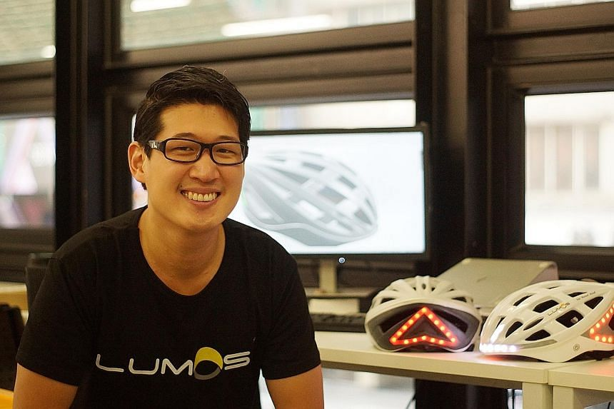 Mr Ding with prototypes of his brainchild, the award-winning Lumos helmet. The bicycle helmet has automatic brake lights and integrated turn signals to improve safety for cyclists.
