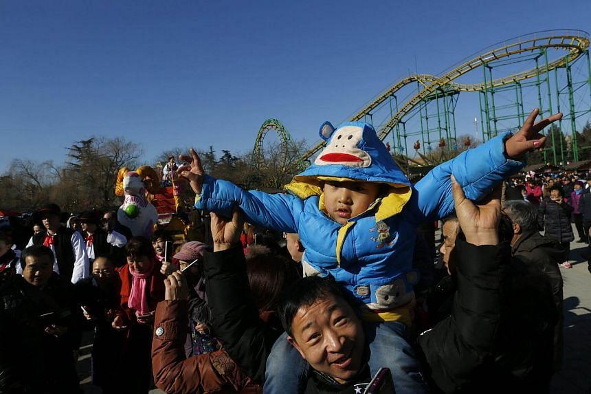 A Chinese man holds up his child to watch a parade at a temple fair celebrating the Spring Festival at the Shijingshan Amusement Park in Beijing, China.