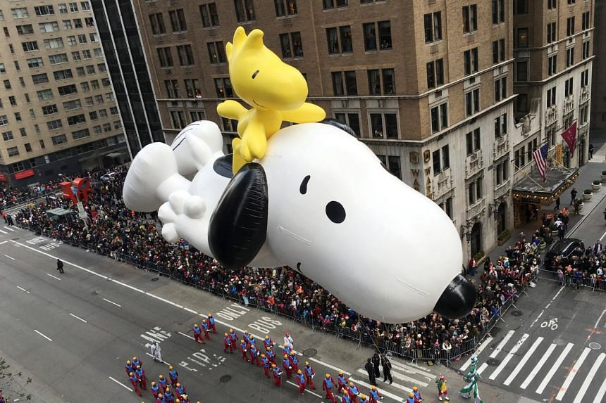 A giant Snoopy and Woodstock float along Manhattan's Sixth Avenue during a Thanksgiving Day Parade on Nov 26, 2015.