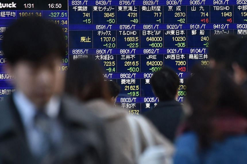 Pedestrians walking past an electric quotation board flashing stock prices on the Nikkei key index of the Tokyo Stock Exchange in Tokyo, on Jan 31, 2017.