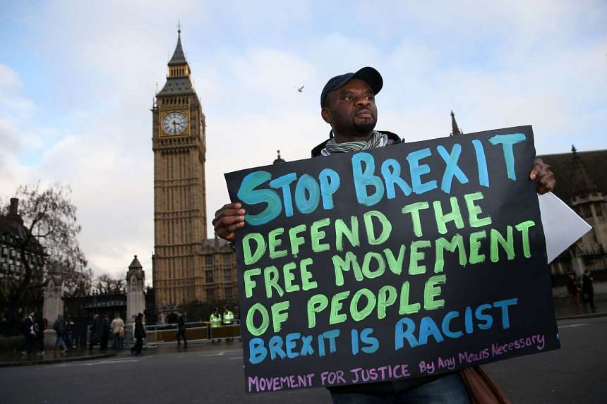A demonstrator holds an anti-Brexit placard outside the Houses of Parliament in London on Feb 1, 2017.