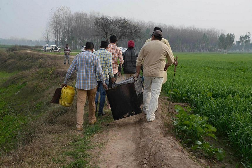 Indian villagers help police to remove equipment used to make raw alcohol during a search at Dhole Wal village in Dharamkot.
