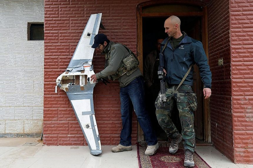 US Special Operations Forces members inspecting a drone used by ISIS militants to drop explosives on Iraqi forces. Few Iraqi and Kurdish units have been equipped with the sophisticated devices that the American troops have to nullify the growing leth